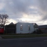 the roof of the church hall gone, beneath a cloudy sky